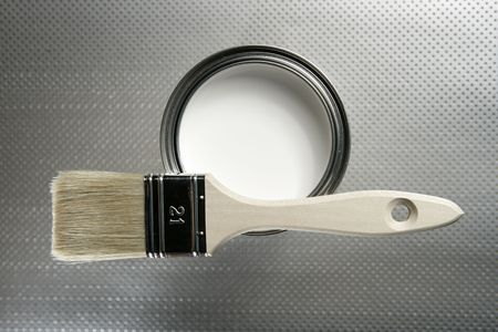 Painter brush and white paint tin macro over silver pattern background photo