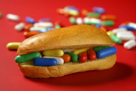 health symbols metaphors: Sandwich made of colorful candy sweet, children favourites menu over red Stock Photo