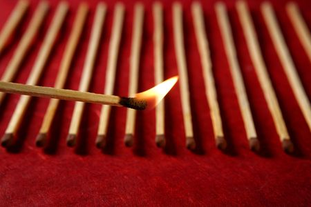 Light wooden matches arrangement in a row over red background photo