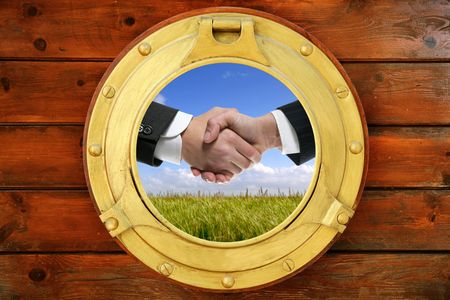 Businessmen green outdoor handshake view from boat round window photo