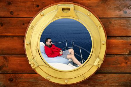 Man relaxed on bean bag over blue sea, view from boat round window photo