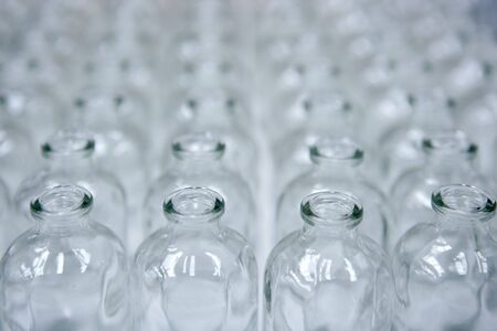 assembly: Glass transparent empty bottles in rows, cosmetics assembly line