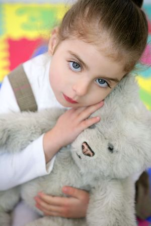 Beautiful preschooler student little girl hug her teddy bear photo