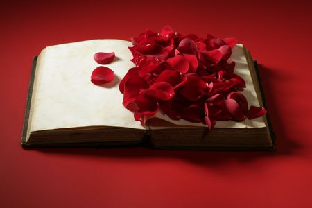 date book: Rose petals over old aged book, red background