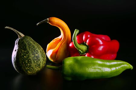 Colorful vegetables still over black, pepper and pumpkin photo