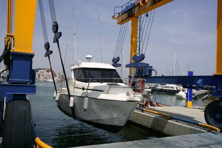 sportfishing: Dock crane elevating a fishing boat in Mediterranean marina