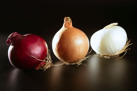 Three colorful different onion  in varied colors over black photo