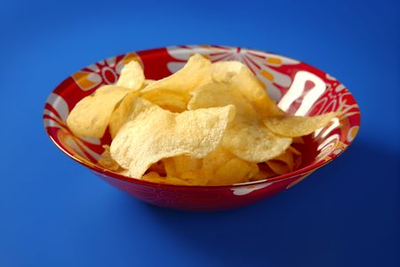 Potato fried chips on red plate over blue background photo