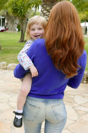 Redhead mother and blond daughter playing on the green park photo