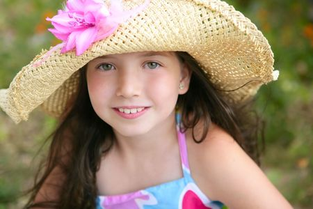 Closeup portrait of beautiful teen little girl with hat in the park Stock Photo