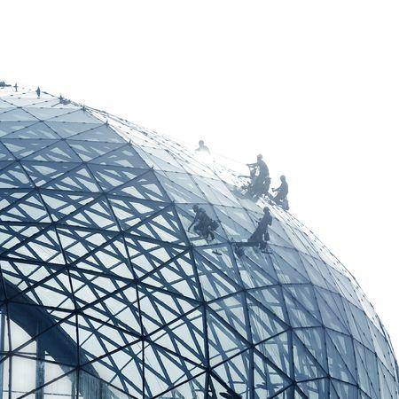 edificio industrial: Trabajadores de limpieza de una fachada de cristal redonda con luz posterior fuerte