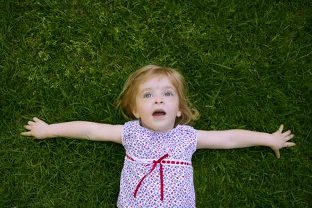 Beautiful little toddler girl happy lying on the green grass photo
