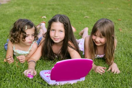 Three little girl outdoor playing with toy computer in grass photo