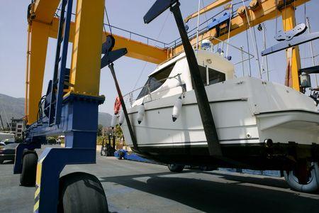 Dock crane elevating a fishing boat in Mediterranean marina photo