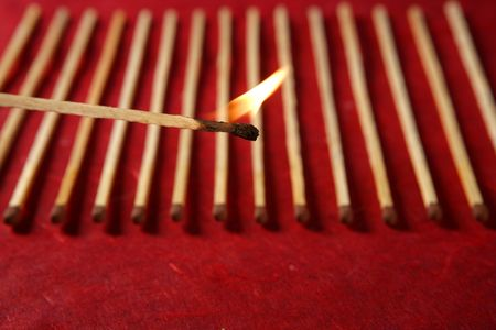 Light wooden matches arrangement in a row over red background Stock Photo - 5164560