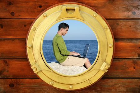 Businessman with computer on the beach, view from round boat window photo