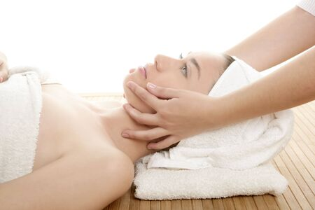 Beautiful woman face massage with towel around her head photo