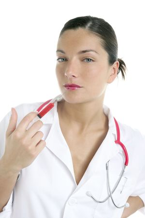 Doctor woman with red syringe and needle in her lips over white background photo