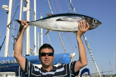 Big game fisherman with saltwater tuna catch in his hands photo