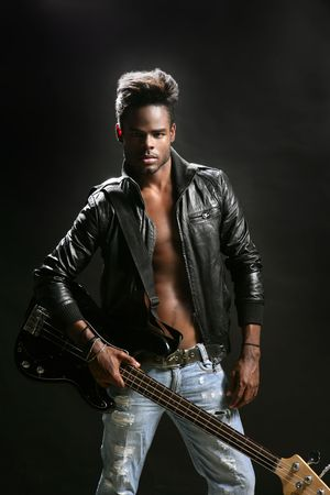 Afro american rock star musician with leather jacket and bass guitar photo