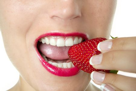 Beautiful woman eating a red strawberry over white background photo