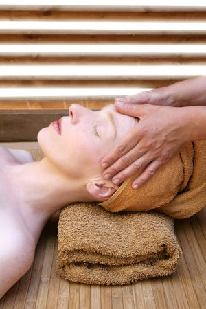 Beautiful woman portrait relaxing massage on her head in warm colors photo