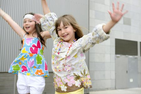 little girl dancing: Two little girls dancing in the city with gray building in background Stock Photo