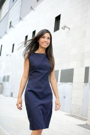 woman street: Beautiful blue dress stewardess walking to convention center Stock Photo