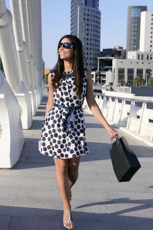 Beautiful brunette shopaholic outdoor modern city urban street photo