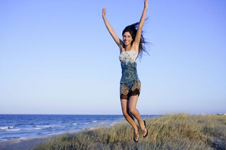 Beautiful brunette jumping in the summer blue beach photo