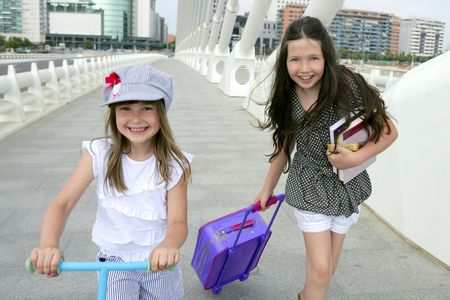 Little girls going to school with bags, books and student stuff photo