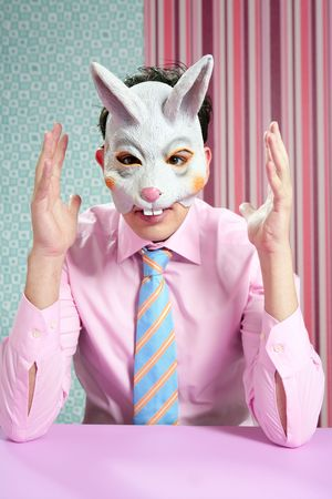 Businessman with funny rabbit mask portrait over wallpaper photo