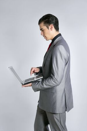 Businessman in gray suit holding laptop computer at studio Stock Photo - 5258133