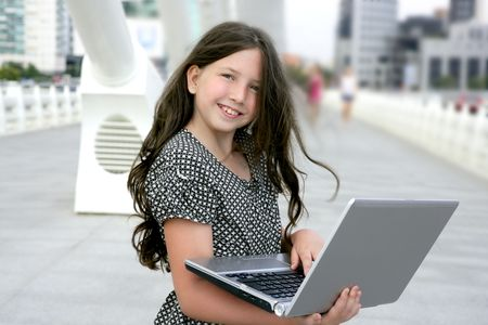 little town: Beautiful little girl with laptop computer downtown city bridge Stock Photo