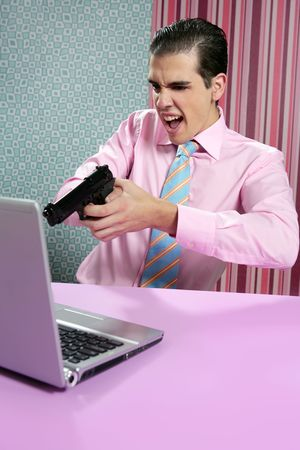 businessman young shooting handgun with computer pink bacground photo