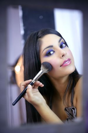 Indian fashion model makeup with brush on the mirror photo