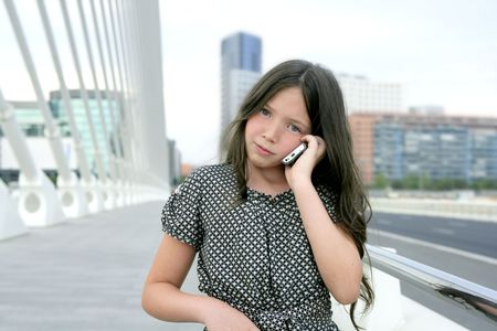 Adorable teenager little girl talking phone downtown in city bridge photo