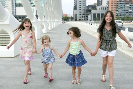 Four little girl group walking in the city bridge downtown buildings Stock Photo - 5363145