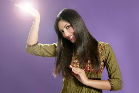 Beautiful indian young brunette woman posing hands on purple background photo