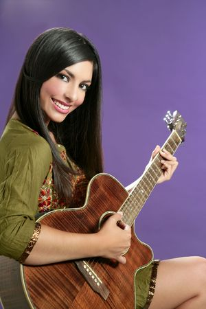 Beautiful brunette playing acoustic guitar over purple background photo