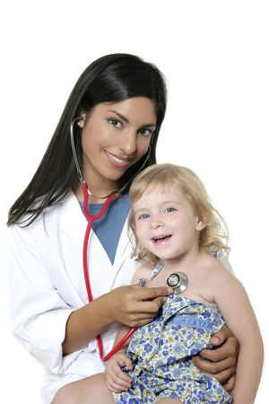 pediatrics: Brunette pediatric doctor with blond little girl on medical exam Stock Photo