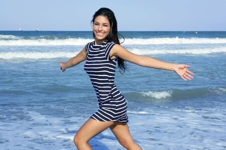 Beautiful summer indian brunette girl jumping on the blue beach photo