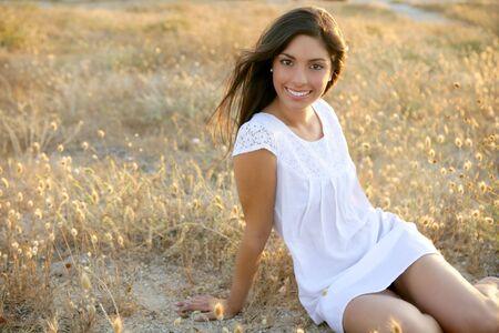 Beautiful indian brunette having a rest on a golden summer field photo