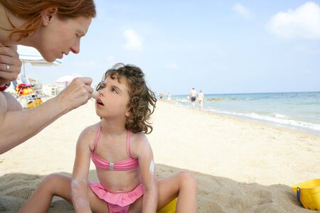 Daughter and mother on the beach sun screen protection moisture cream photo