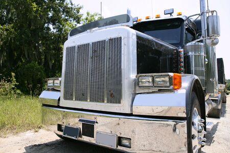 trucker: Black huge lorry american truck with stainelss steel in green outdoor