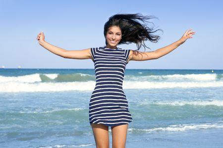 Beautiful summer indian brunette girl jumping on the blue beach photo