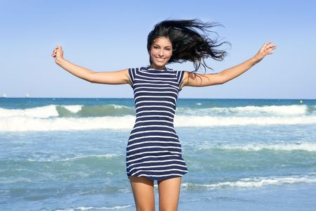 Beautiful summer indian brunette girl jumping on the blue beach Stock Photo