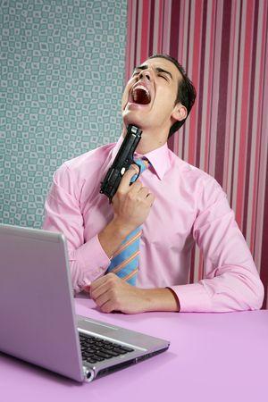 businessman young shooting handgun with computer pink bacground photo