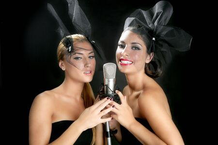 Beautiful women couple singing on a vintage microphone on black background photo