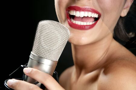 female singer: Beautiful woman singing on a vintage microphone on black background Stock Photo